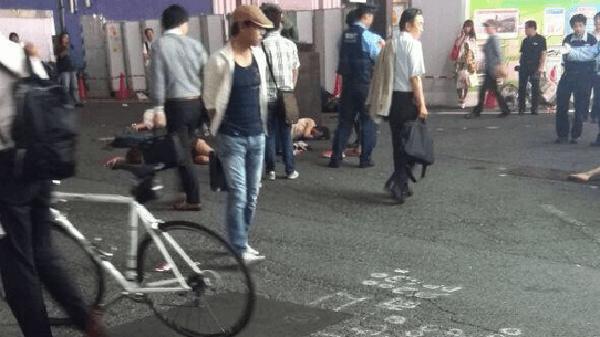 昏倒している女子大生らを眺める通行人の画像