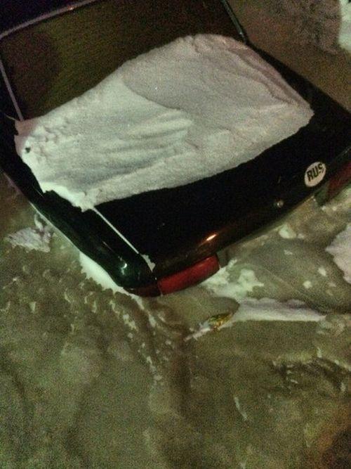 水が凍って車が飲み込まれている画像