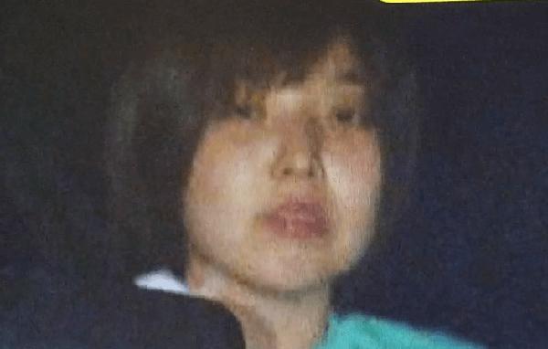 察警車両のなかからカメラ目線の木口光子容疑者の顔写真画像