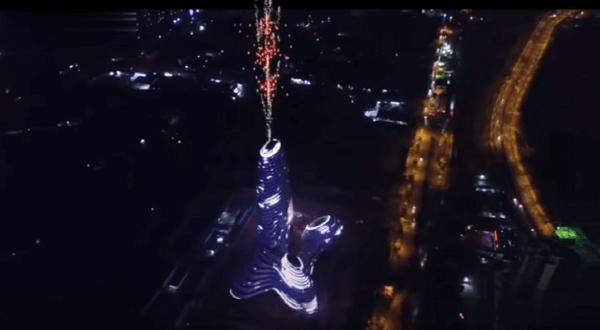 高層ビルの屋上から花火が打ち上がっている写真画像