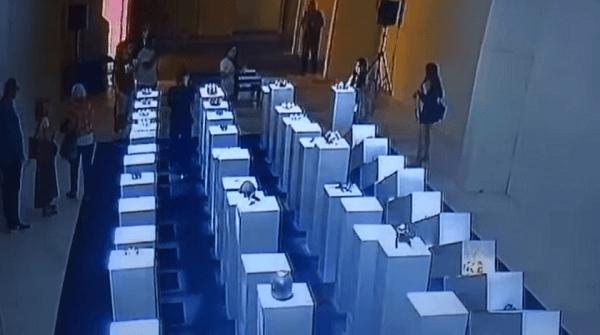 女性がドミノ倒しとなった展示品を直すキャプチャ画像