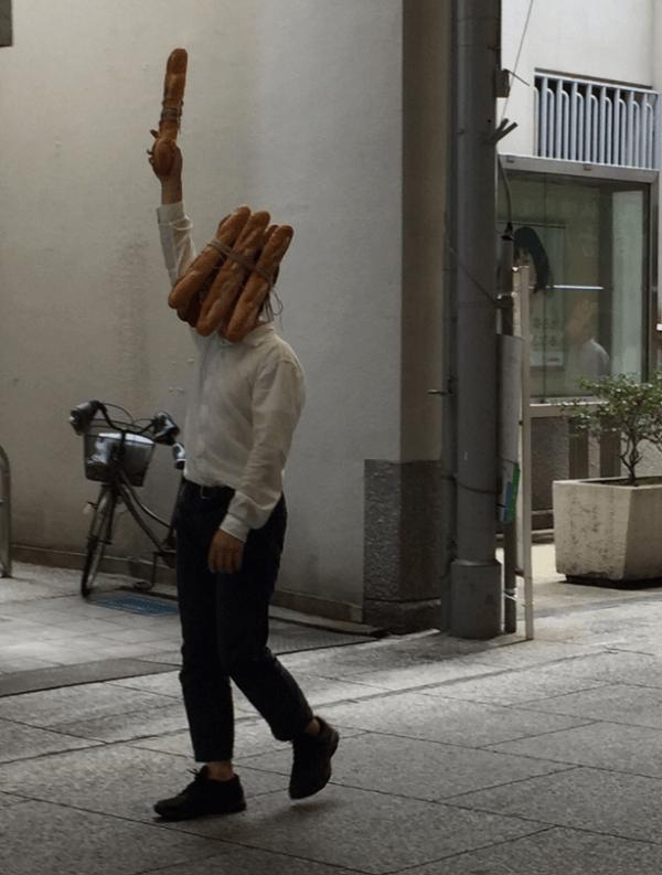 フランスパンを頭にくくり付け歩く男性の画像