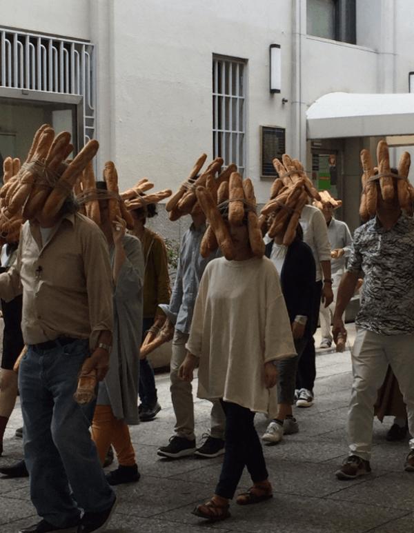 尾道の商店街を歩くフランスパンの団体の画像