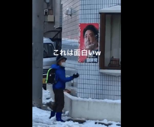 小学生が安倍総理のポスターに雪を投げつける動画のキャプチャ画像