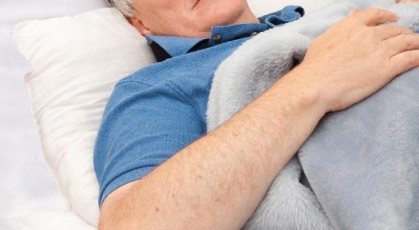 布団で寝ている男性の写真画像