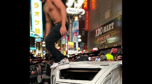 若者が軽トラを横転させて上に乗っている写真画像